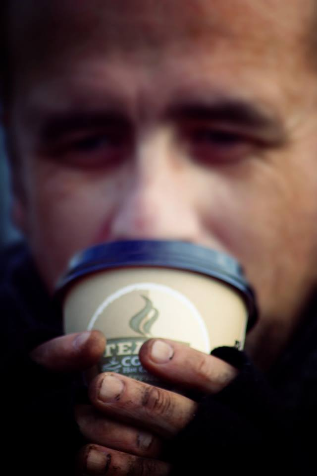 homeless man drinks coffee